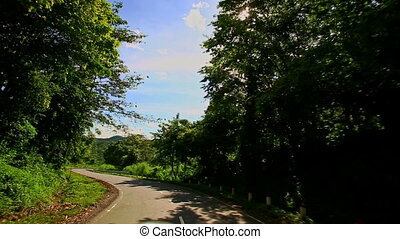 Camera Moves along Curvy Country Road among Hilly Landscape...