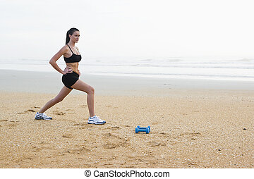Beautiful young woman exercising on beach - Portrait of...