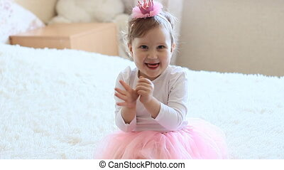 Beautiful funny little girl claps her hands and laughs. -...