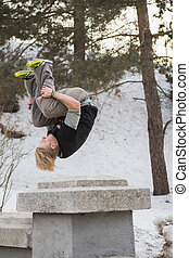 Teenager blonde hair man training parkour jump in the snow...