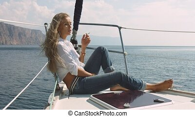 The girl smokes on a yacht - Young sexy girl smokes on a...