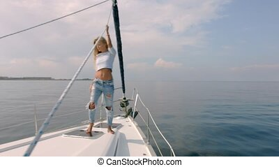Young lady relaxing on the moving yacht in sea at sunny day...