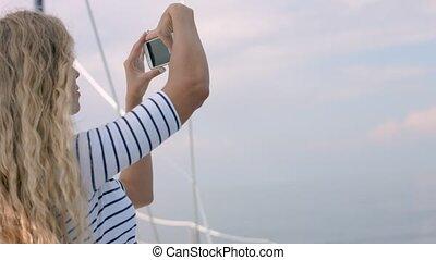 Young woman taking photo of beautiful sea lagoon on...