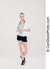 healthy sports woman in fitness clothes with gym towel and water bottle