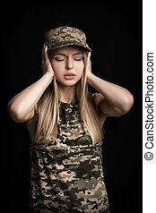 portrait of woman soldiers in military attire closes his ears with hands on black background