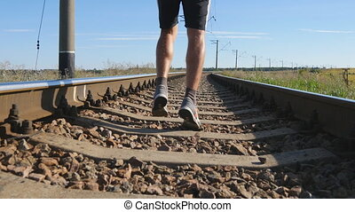 Male feet are running between rails on railroad tracks. Sprinting runner man jogging on railway sleepers. Legs of sport athlete training outdoor at summer. Active healthy lifestyle outside. Close-up