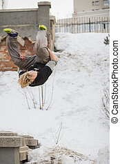Teenager blonde hair guy training parkour jump flip in the...