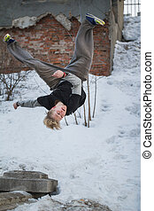 Backflip parkour in winter snow park - blonde hair teenager,...