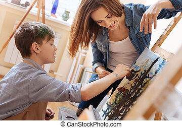 Helpful young woman teaching painting kid at school