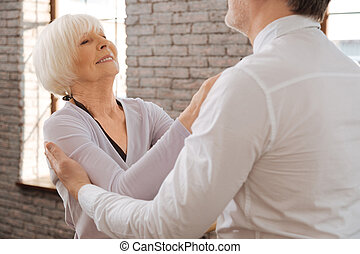 Smiling aged couple waltzing in the dance studio