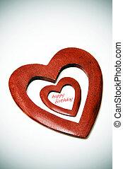 happy birthday written inside a wooden heart