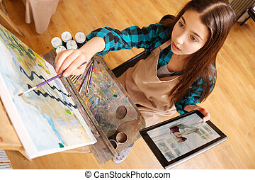 Concentrated girl painting in the art studio - Using gadgets...