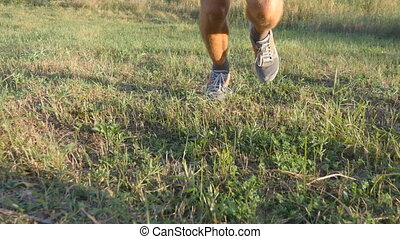 Male feet running over green hill. Legs of athlete is jogging in nature at sunset. Sports runner jogging uphill outdoor. Meadow with green grass. Cross-country training. Healthy lifestyle. Close-up