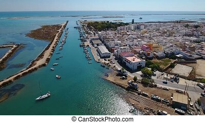 Aerial. Fishing port in village of Fuseta, view of bay and...