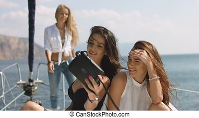 Girls taking selfies on yacht. Young models on vacation
