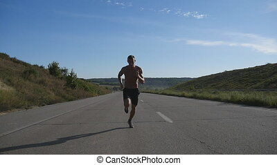 Sprinting runner man jogging at highway. Male sport athlete training outdoor at summer. Young strong muscular guy exercising on rural road during workout. Active healthy lifestyle outside. Slow motion