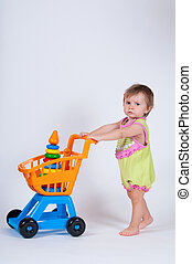 Baby girl with toy shopping cart. Isolated on white background.