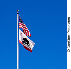 American and California State Flags Waving Before a Clear...