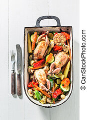 Roasted quails with spices and vegetables in casserole