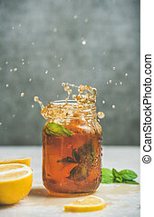 Iced tea with bergamot, lemon, mint in jar with splashes -...