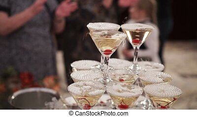 People taking glass of champagne from pyramid at the party