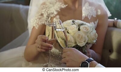 Bride and groom clinking glasses with champagne indoors