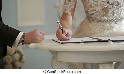 Bride and groom signing documents on wedding ceremony