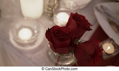 Red roses anf candles on table on the party