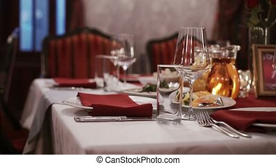 Plate and glasses on red tablecloth in restaurant