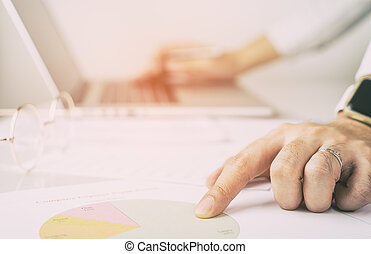 Office worker is pointing and analyzing paper chart...