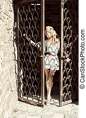 A young woman holds her hands behind the bars the door