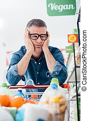 Sad man shopping at the supermarket