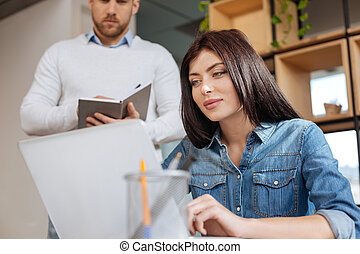 Beautiful delighted woman looking at the laptop screen
