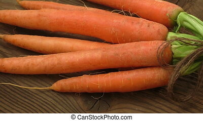 Fresh organic carrots with green tops and twine on wooden...