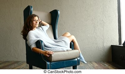 Young woman relaxing in the armchair - Young woman relaxing...