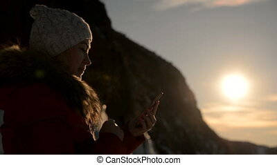 The girl is using the smartphone at sunset. - Tourist girl...