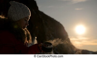 The girl is drinking tea at sunset. - Tourist girl drinks...