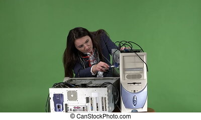 Frustrated woman office worker trying to repair computer system unit