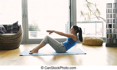 Young woman exercising at home, doing crunches. - Beautiful...