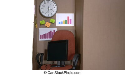 Very small office in a cardboard box on white background -...