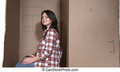 Woman drawing flower on a wall of cardboard box as her tiny...