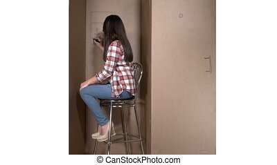 Happy woman living in a cardboard box draws a flower in...