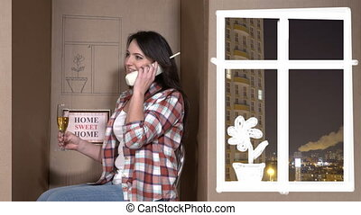 Happy woman talking on the phone in a cardboard box as her...