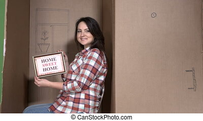 Woman with picture frame HOME SWEET HOME inside cardboard...