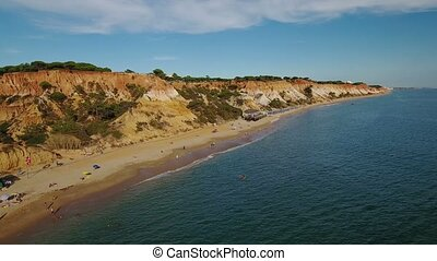 Aerial. Beach of Falesia and tourists are resting. View from...