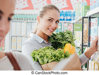 Women shopping together at the supermarket - Friends doing...