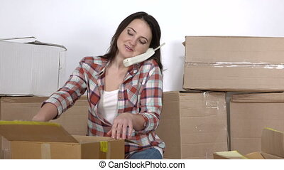 Woman on the phone unpacks moving cardboard boxes on the...