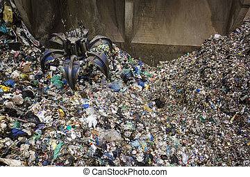 Mechanical claw hand grabbing pile of mixed waste, deposited...