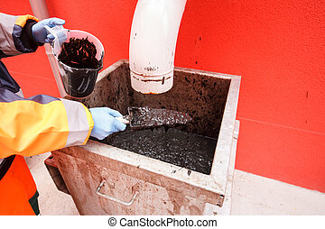 Worker collecting mud from biodegradable waste pool at waste...