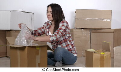 Woman moving in a new apartment packing and taping cardboard...